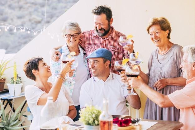 ワイングラスを乾杯し、家のオープンテラスで集まりを祝う多世代の白人家族。愛する家族がワインを飲み、一緒に余暇を楽しんでいます