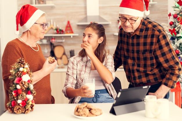 クリスマスの日にデザートを楽しむ多世代家族