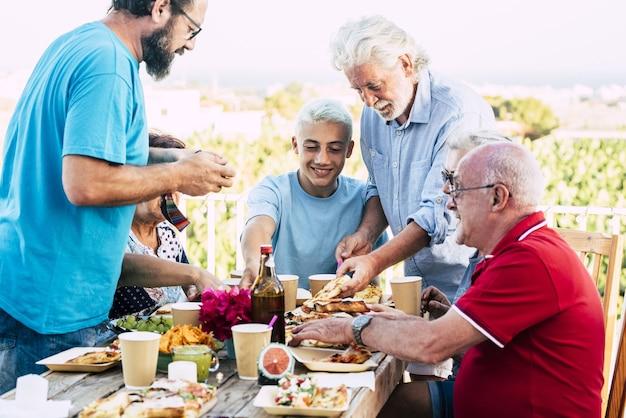 夏休みの屋外で食べ物や飲み物のパーティーを楽しむ多世代家族。屋外のテーブルの設定で食事をする余暇を過ごす幸せな家族