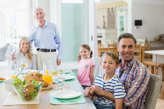 自宅のダイニングテーブルで食事をしている多世代家族