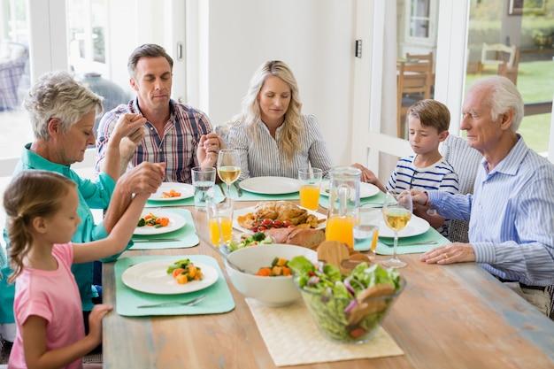 ダイニングテーブルで食事をしている多世代家族