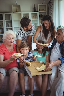 Multi-generation family having pizza in living room