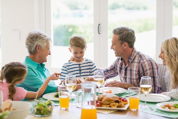 ダイニングテーブルで食事をしながら相互作用する多世代家族