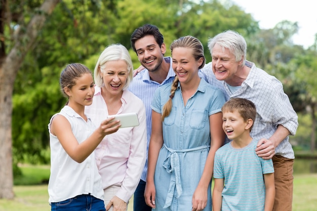 Multi-generation family looking at mobile phone