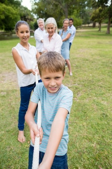 Multi-generation family pulling a rope in tug of war