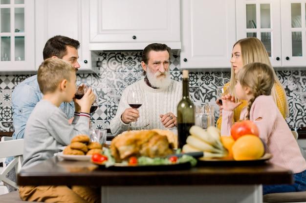 多世代家族がグラスを上げて、感謝祭のディナーテーブルで乾杯します。祖父、親と子が一緒に夕食をとる