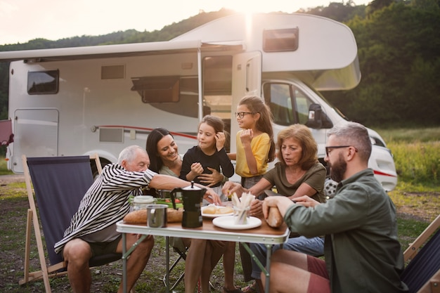 A multi-generation family sitting and eating outdoors by car, caravan holiday trip.
