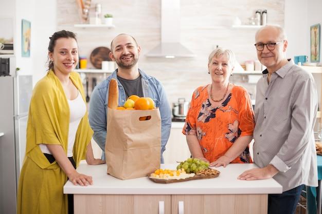 Семья нескольких поколений улыбается, глядя на камеру на кухне.