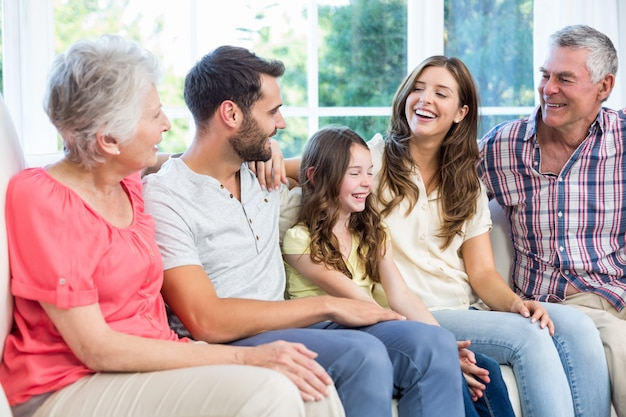 Multi-generation family smiling while sitting on sofa