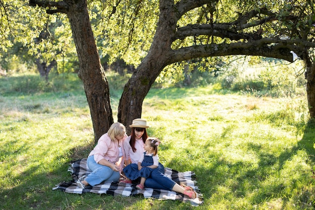 Multi-generation family spending time outdoors in sunny summer garden, sitting on checkered blanket under the big apple tree. mature grandmother with daughter and granddaughter in park.