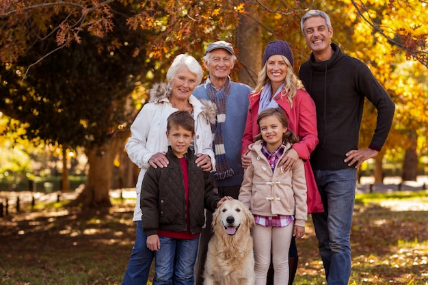 Multi-generation family standing with dog at park