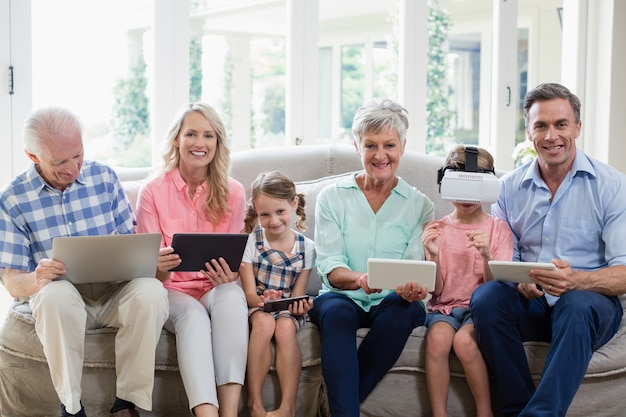 リビングルームでデジタルタブレット、携帯電話、仮想ヘッドセットを使用する多世代家族