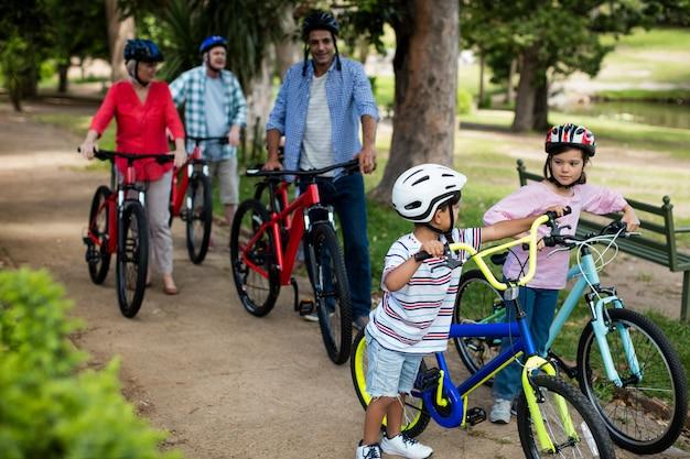 Семья нескольких поколений гуляя с велосипедом в парке
