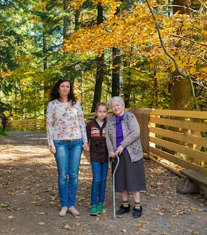 A multi generation photo of a happy grandmother with her daughter and granddaughter outdoor