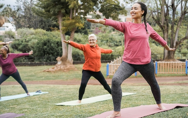 Multi generational people doing yoga class keeping at city park