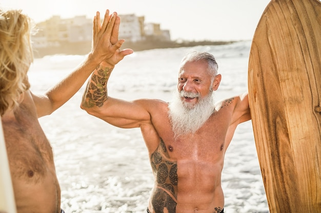 Multi generational surfer friends hands five on the beach after surf session - focus on senior man face