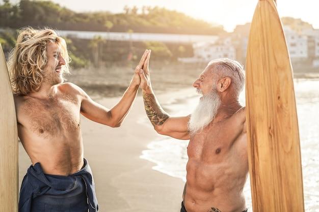 여러 세대의 서퍼 친구들이 서핑 세션 후 해변에서 다섯 손을 잡고 - 노인 얼굴에 초점