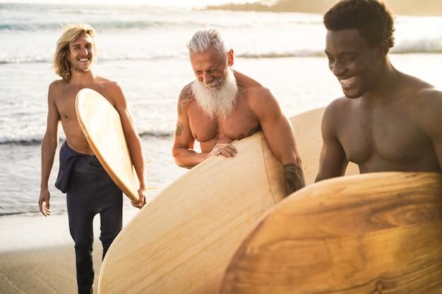 サーフセッションの後にビーチで楽しんでいる多世代のサーファーの友人-年配の男性の顔に焦点を当てる