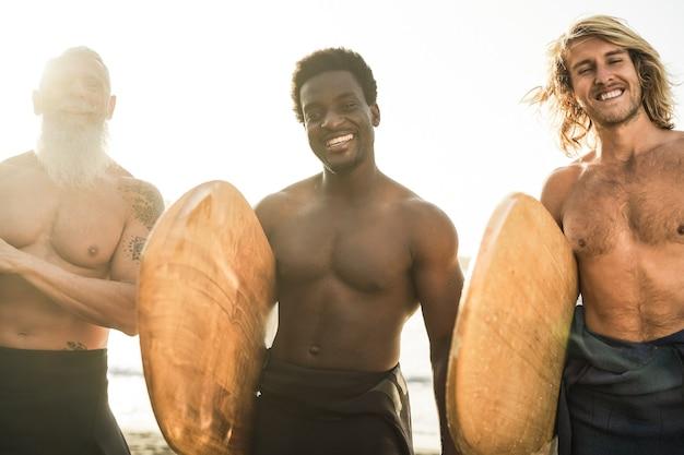 サーフセッションの後にビーチで楽しんでいる多世代のサーファーの友人-右の人にソフトフォーカス