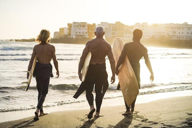 ビーチでサーフィンをしながら楽しんでいる多世代のサーファーの友人-主な焦点は年配の男性