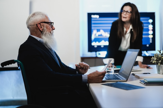 Multi generational trader team making stock market analysis conference inside hedge fund office - focus on senior man face seated in wheel chair