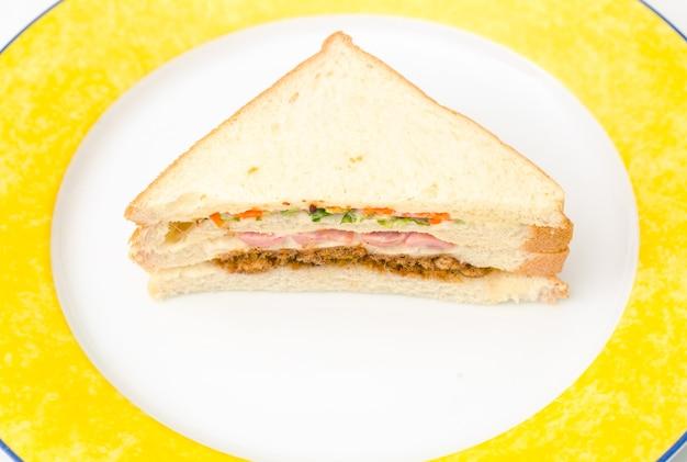 Многослойный бутерброд с ветчиной в керамической тарелке