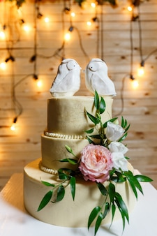 Multi level wedding cake, decorated with flowers, greenery and creative birds topper