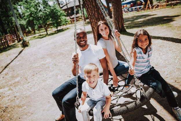 Multi racial family in park african on web swing