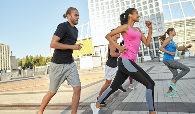 Multi racial young sportsmen running along sunny city