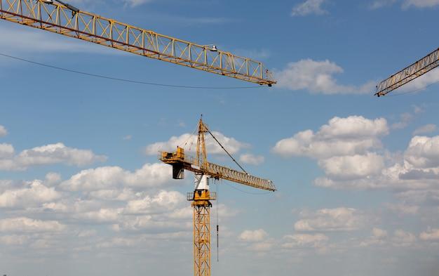 다층 건물 개념: 하늘과 구름 배경 건설 현장의 타워 크레인