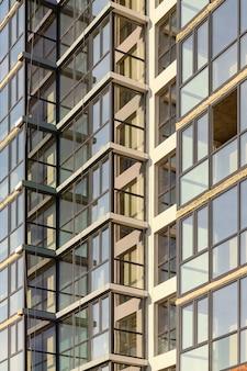 많은 유약 발코니와 창문이있는 다층 건물 외관.