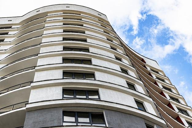 Многоэтажный современный жилой дом на фоне голубого неба. жилищное строительство. жилой фонд. спальный район. ипотечные кредиты для молодых семей.
