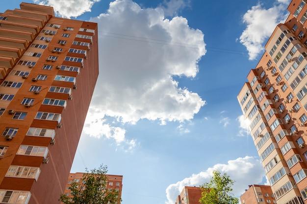 Вид снизу вверх на многоэтажный панельный дом сквозь кроны деревьев. видны белые облака и голубое небо. есть место для текста.