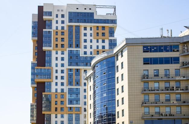 Многоэтажный жилой комплекс на фоне неба. многоквартирный жилой дом. квартиры, офисы, квартиры в многоэтажном доме в синих и коричневых тонах.