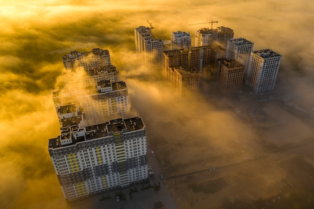 Multi-storey skyscrapers look partly out of the morning mist, the sun's rays shine between the houses.