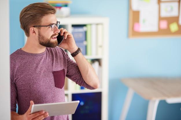 Uomo multi-tasking nel suo ufficio a casa