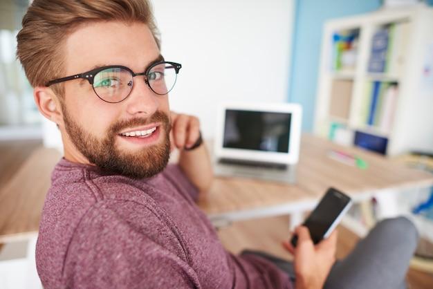 Uomo multi-tasking in ufficio a casa
