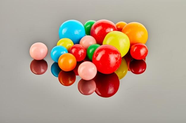 Multi покрашенные шарики жевательной резины на серой предпосылке с отражением.