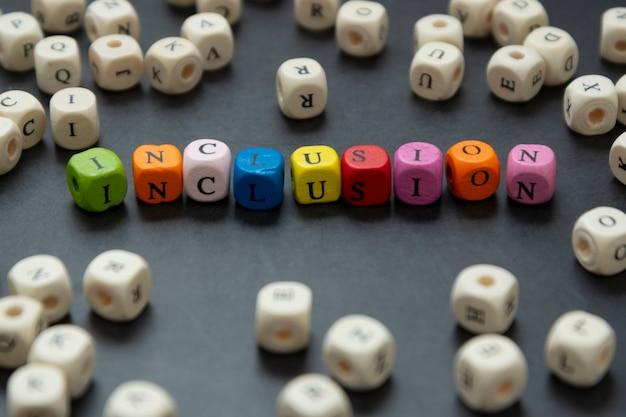Текст включения multi покрашенных кубиков на темной предпосылке. инклюзивная социальная концепция.