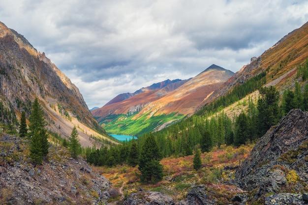 オレンジ色の日当たりの良い山と色とりどりの秋の風景。秋の鋭い山の尾根への壮大なカラフルな景色。秋の色のモトリー山の風景。