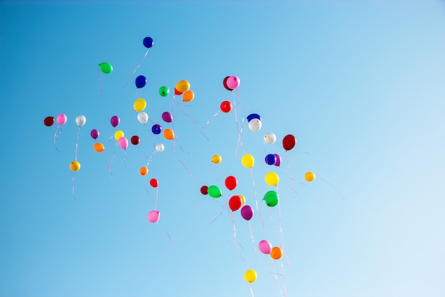 Multicolor balloons fly high clear blue sky. copy space.
