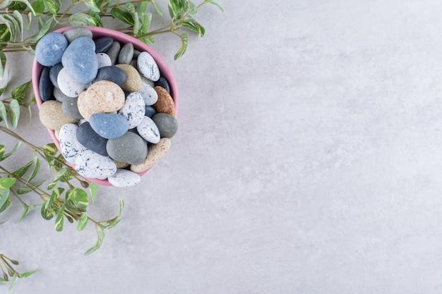 Pietre da spiaggia multicolori per la lavorazione su superficie di cemento