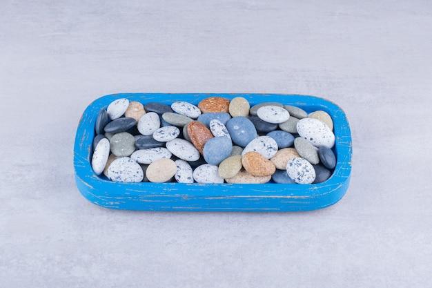 Разноцветные пляжные камни в блюде на бетонной поверхности
