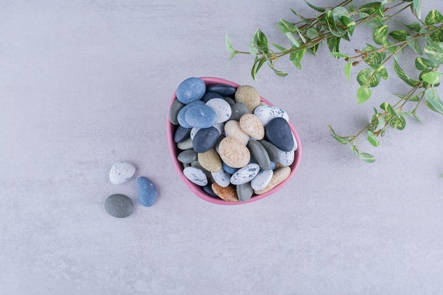 콘크리트 표면에 있는 플래터에 있는 여러 가지 빛깔의 해변 돌