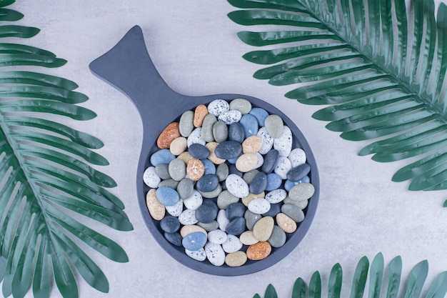Multicolor beach stones in a platter on concrete surface