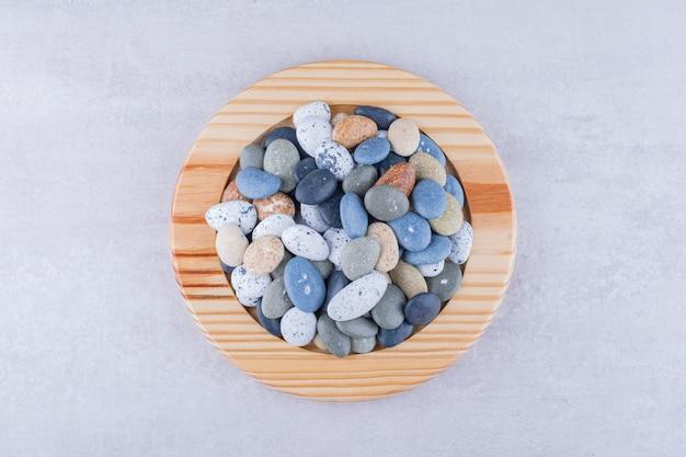 Pietre da spiaggia multicolori in un piatto su una superficie di cemento