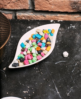 Multicolor bonbon sweets (ball candies) inside white plate bowl on stone brick