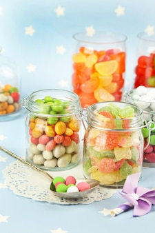 Multicolor candies in glass jars on colorful surface