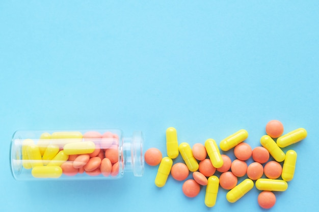Multicolor capsules from glass bottle on blue