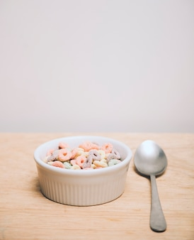 Multicolor cereals in the white bowl and spoon on wooden desk against white background
